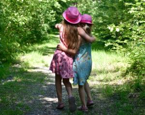 Twee meisjes lopen samen door een bos.